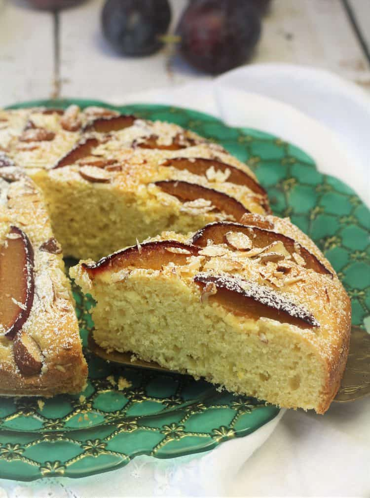 slice of plum almond cake cut from whole cake