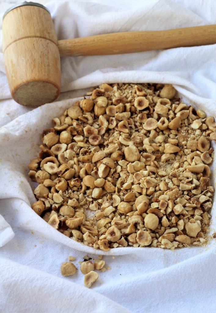 coarsely crushed hazelnuts on dish cloth with meat mallet on side