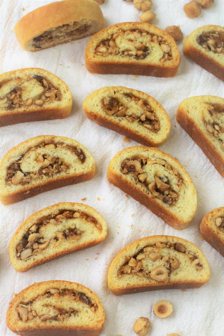 wedges of hazelnut and jam filled roll cookies on white dish towel with hazelnut halves