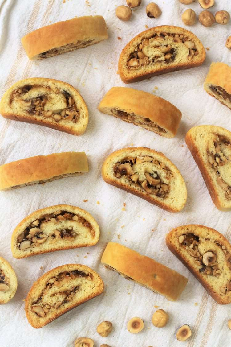sliced roll cookies filled with hazelnuts and jam on white dish cloth