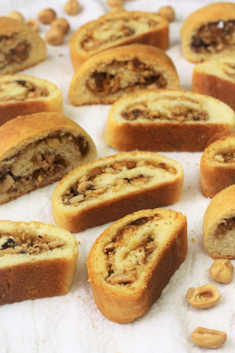 sliced biscotti filled with hazelnuts and jam on dish cloth with halved hazelnuts