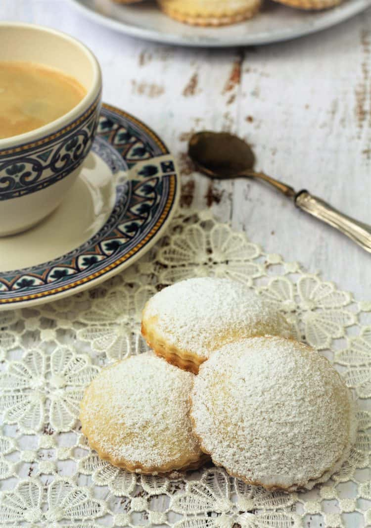 genovesi ericine cookies on lace doily next to coffee cup and spoon