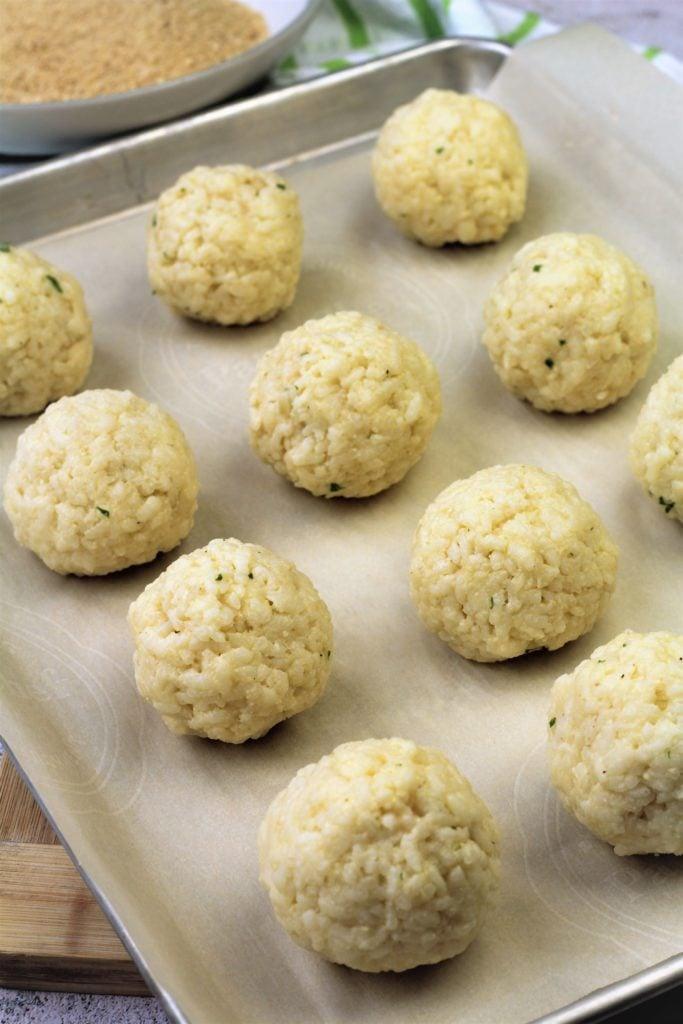 assembled arancini balls on baking sheet