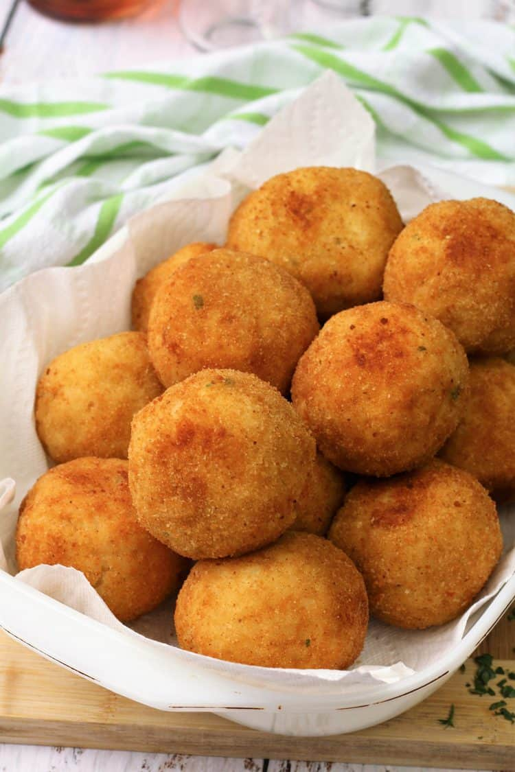 seafood arancini balls piled on paper towel lined dish