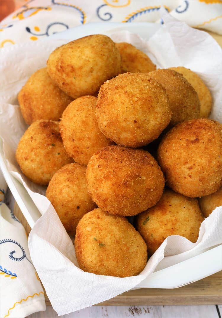 arancini piled on paper towel lined tray