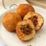 halved arancini filled with meat sauce and peas on white plate