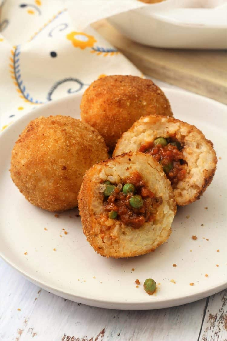 halved Sicilian arancini with meat sauce and peas filling on white plate with 2 whole arancini