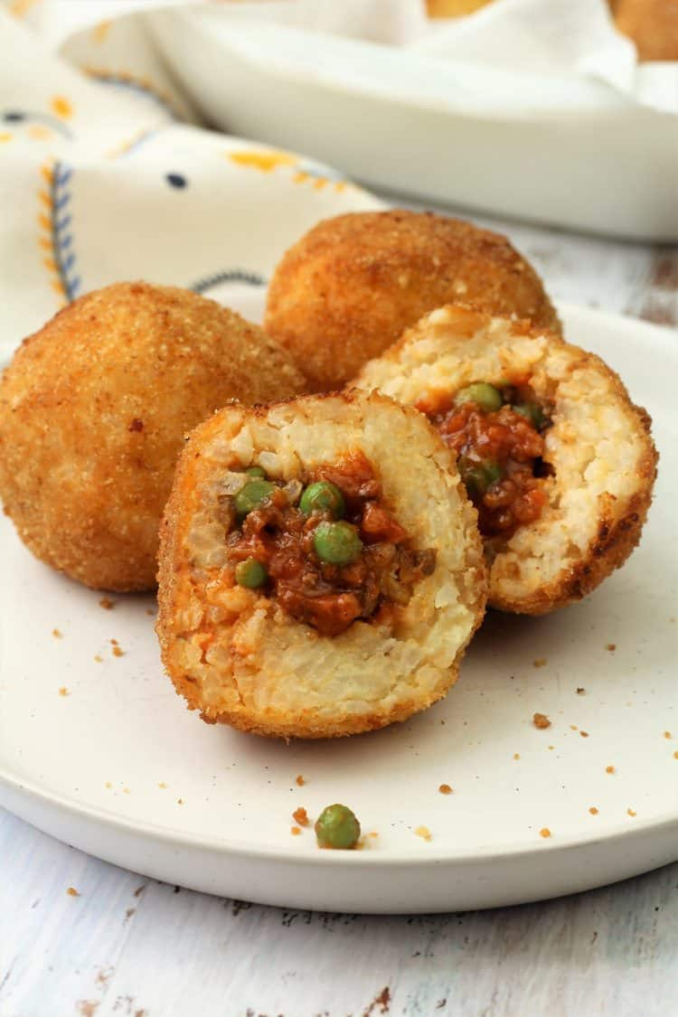 halved arancini with meat sauce and peas filling on plate with 2 whole arancini