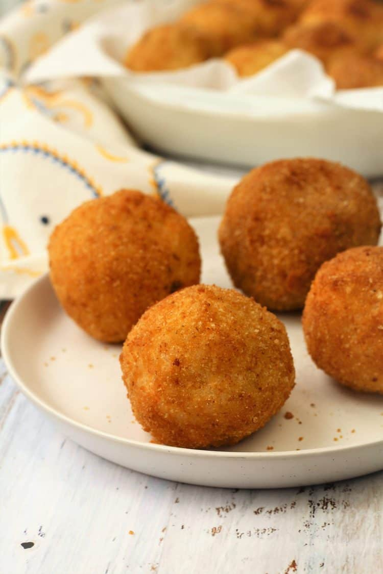4 arancini on white plate with platter full in background