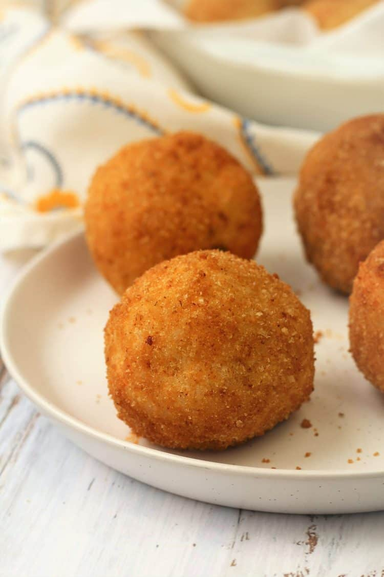 rice balls, or arancini, on white round plate