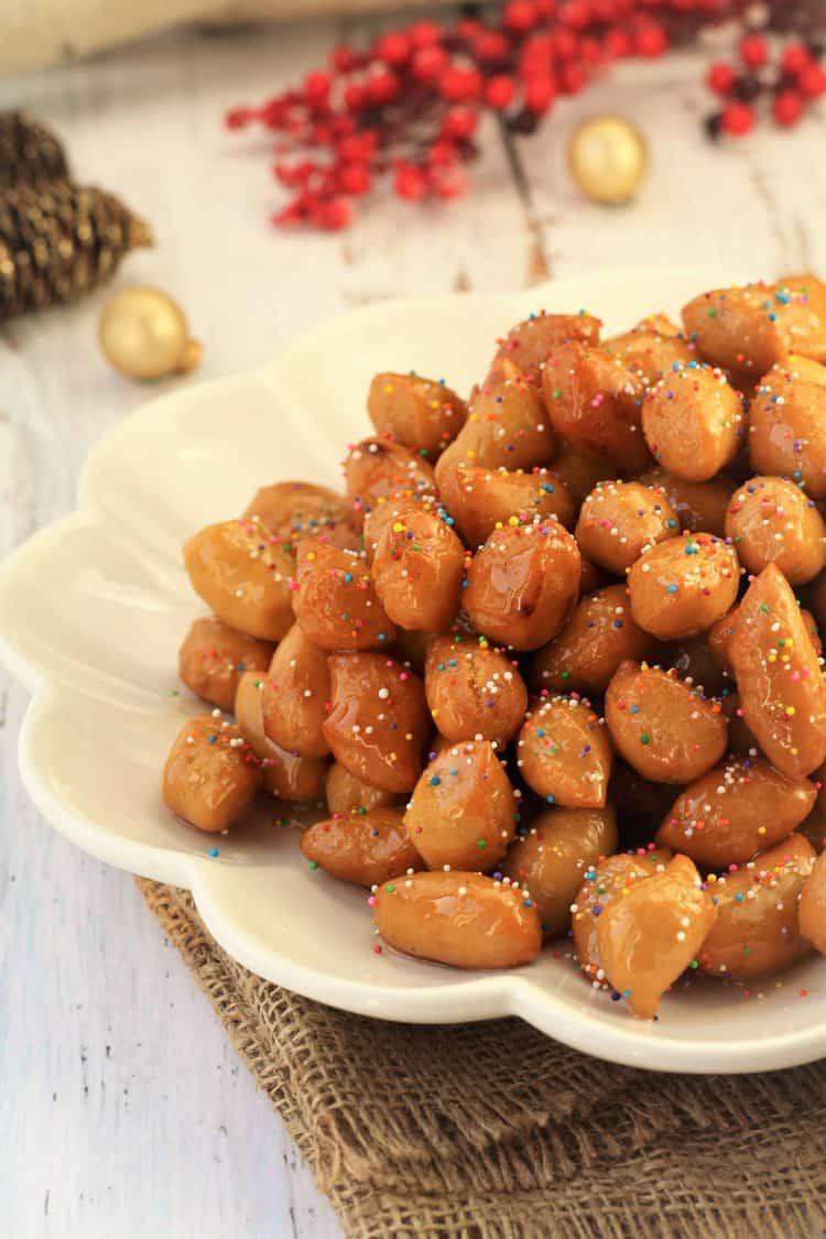 pignolata honey balls piled in a mound on white scallop edged plate