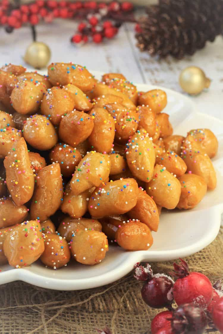 pignolata honey balls in a mound on white plate sprinkled with candy sprinkles