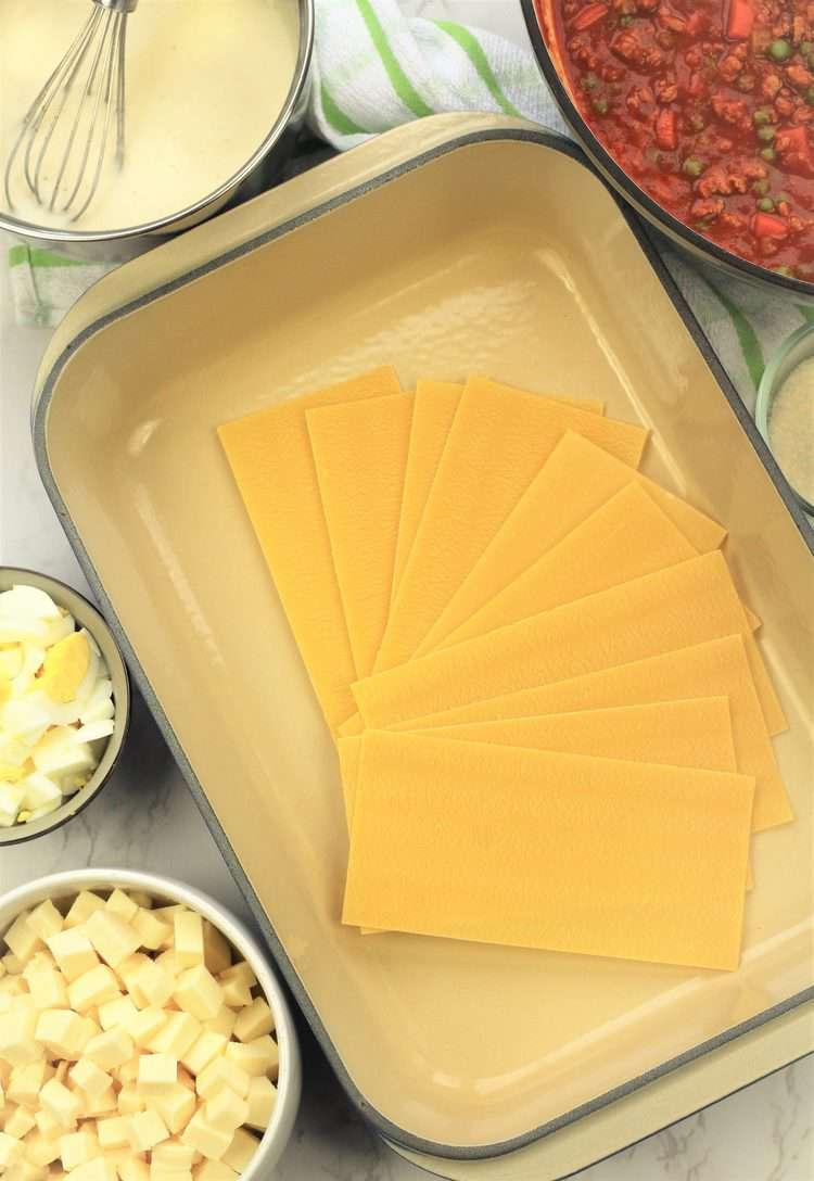 lasagna pan with lasagna sheets surrounded by bowls of ingredients