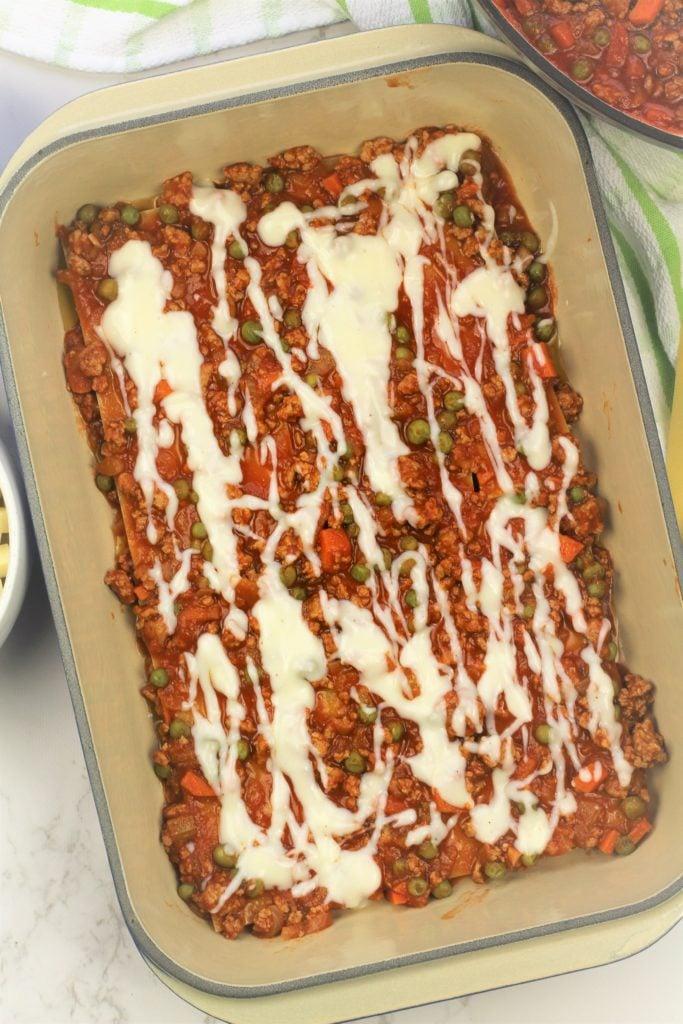 bechamel drizzled over lasagna