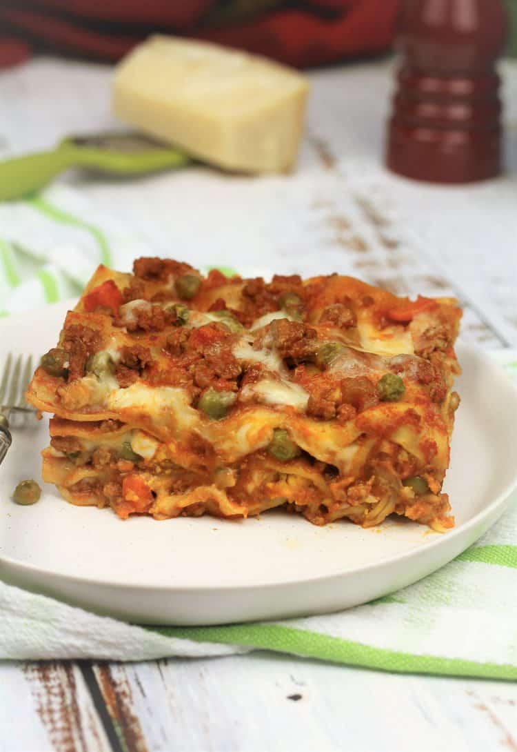 slice of Sicilian lasagna on white plate with fork