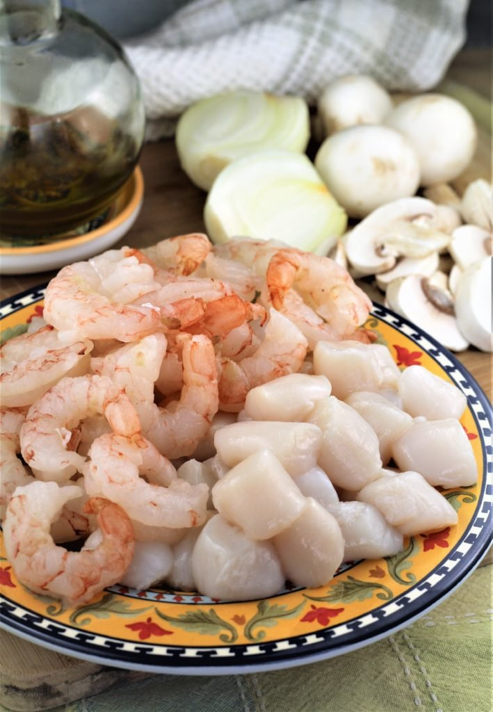 raw shrimp and scallops on plate surrounded by sliced mushrooms and onions